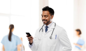 smiling indian male doctor with smartphone