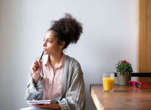 33727926 - portrait of a young woman sitting at home with pen and paper