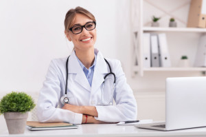 Female Physician Smiling Looking At Camera Sitting In Office